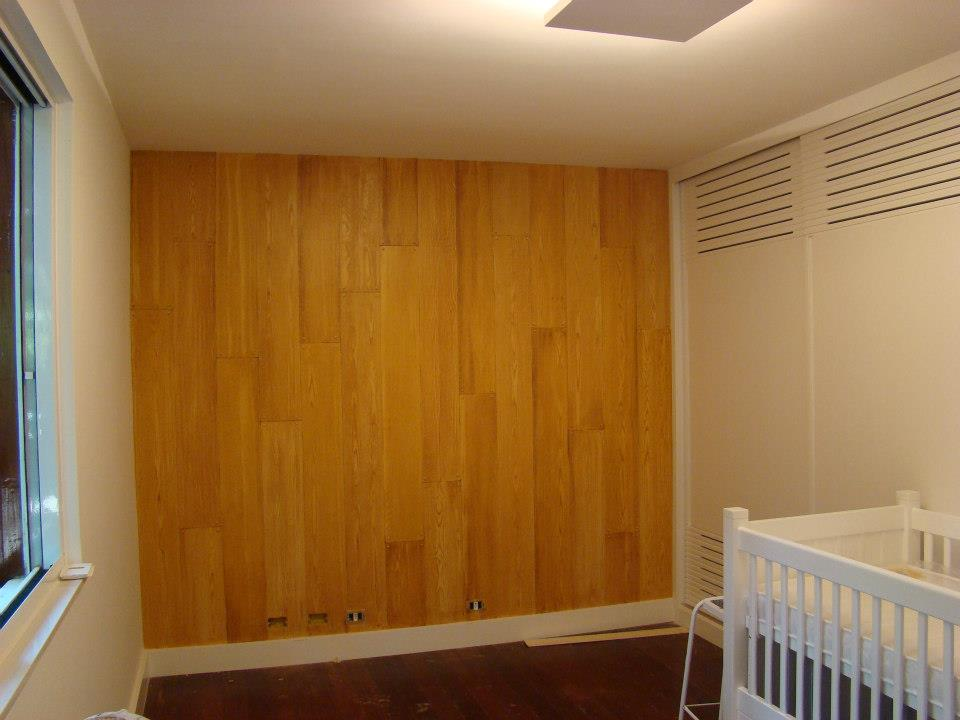 """Quarto de bebê com parede de """"madeira"""""""