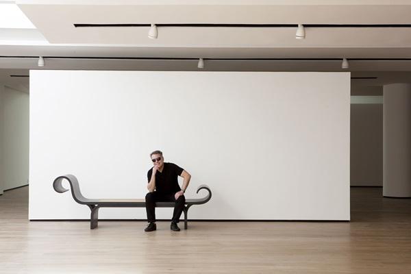 oão Caetano sentado na marquesa assinada por Oscar e Ana Maria Niemeyer na nova loja Arquivo Contemporâneo